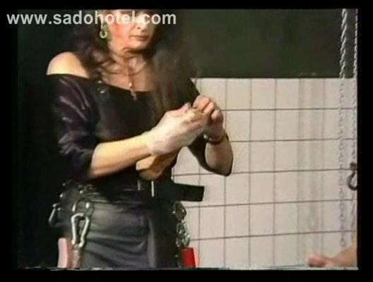 woman dressing on leather puts plastic cock into
